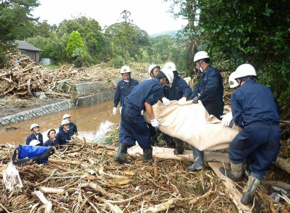 Rescue workers recover the body of a victim from a site that was damaged by a landslide caused by Typhoon Wipha in Izu Oshima island, south of Tokyo.