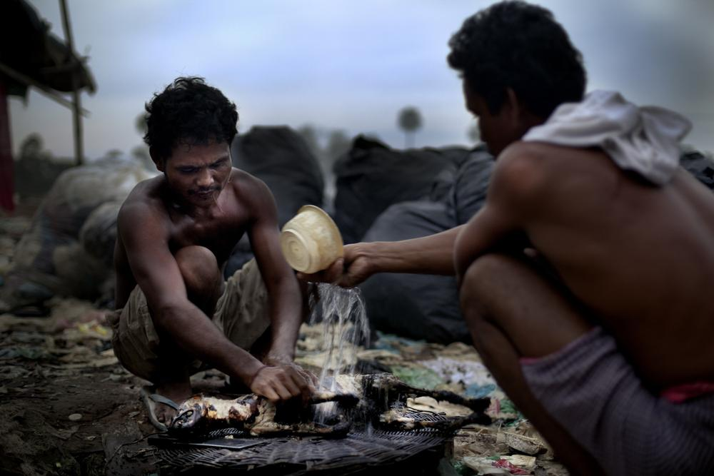 <p>Two residents of the Anlong Pi rubbish dump in Siem Reap prepare their dinner. Meat is rare in their daily meals. Often small children hunt mice using slingshots, and for special occasions, residents buy stray dogs to kill and consume from nearby villages for $10.</p>
