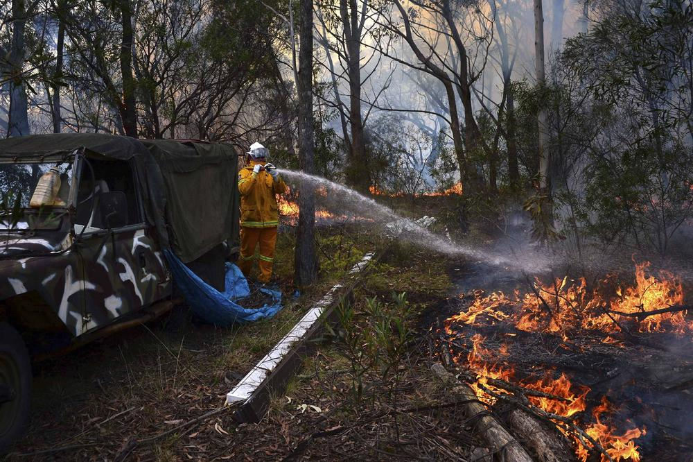 <p>A Rural Fire Service firefighter sprays water onto a small fire burning near a home in western Sydney, Australia. A state of emergency was declared in the state of New South Wales.</p>