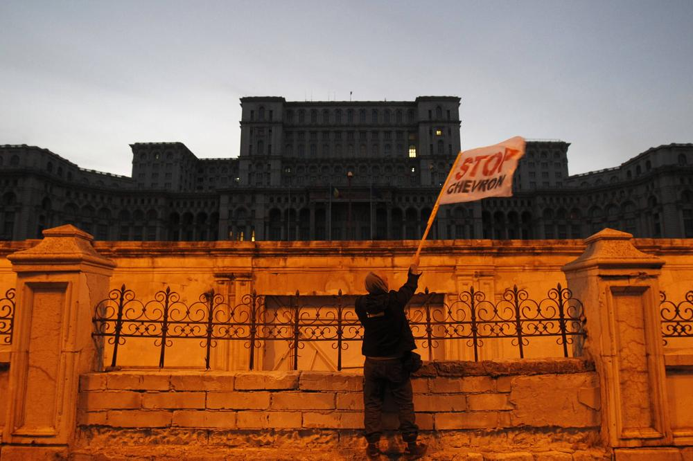 <p>A man waves a flag in front of Romania\(***)s parliament during a protest against plans by US energy group Chevron to explore for shale gas in a poor eastern region and a Canadian company\(***)s project to set up Europe\(***)s biggest open cast gold mine in Romania.</p>