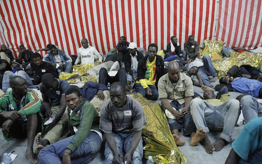 <p>Migrants gather aboard the amphibious ship San Marco after being rescued from a boat in distress some 25 miles off the island of Lampedusa, Italy, on October 25, 2013. More than 800 migrants were intercepted trying to cross the Mediterranean Sea during just one mass crossing of four boats.</p>