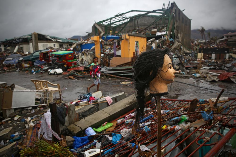 A Typhoon Haiyan survivor carrying her clothes looks at a mannequin\(***)s head which was put on a stick as she walks through the ruins of Tacloban City, on November 22, 2013.