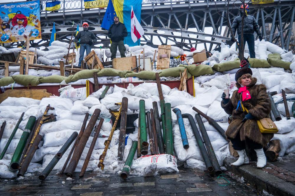 "<p>Five volunteers guard the new barricade, under an ""Angry Ukrainians"" billboard.</p>"
