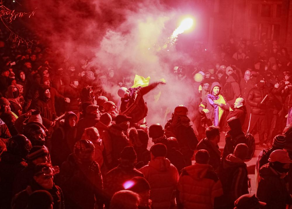 A man throws a flare towards Interior Ministry members during a rally held by supporters of EU integration in Kiev on December 1. Ukrainian opposition leaders called for President Viktor Yanukovich and his government to resign at a rally of about 350,000 people, the biggest protest in the capital since the Orange Revolution nearly a decade ago.