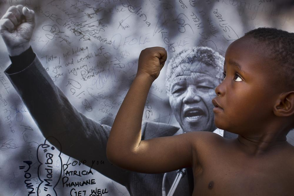 A young member of the Maitibolo Cultural Troupe, in front of a placard of Mandela.