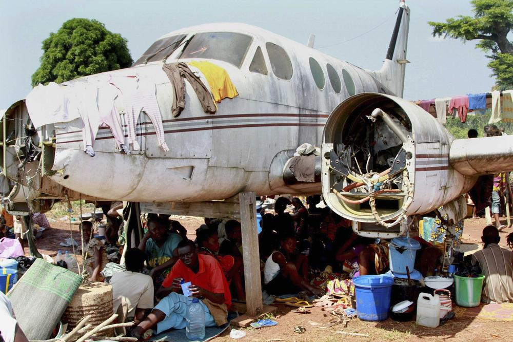 <p>People displaced by fighting between rival militias take shelter under an old broken airplane at the airport in Bangui, the capital of the Central African Republic. Anarchy and violence have been widespread across the country since the president was overthrown in March.</p>