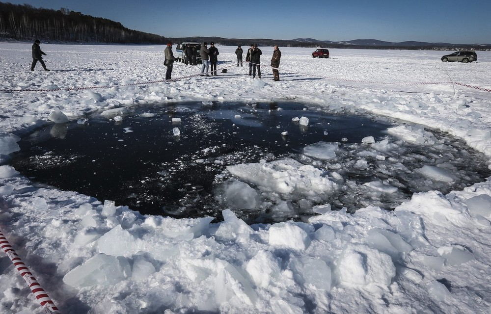 A Russian policeman stands near an eight-metre hole, reportedly the site of a meteorite fall, in the ice of a frozen lake in Russia\(***)s Ural region. Approximately 1,000 people were hurt in the area, mostly by shards of flying glass following the shock wave from the meteorite strike.