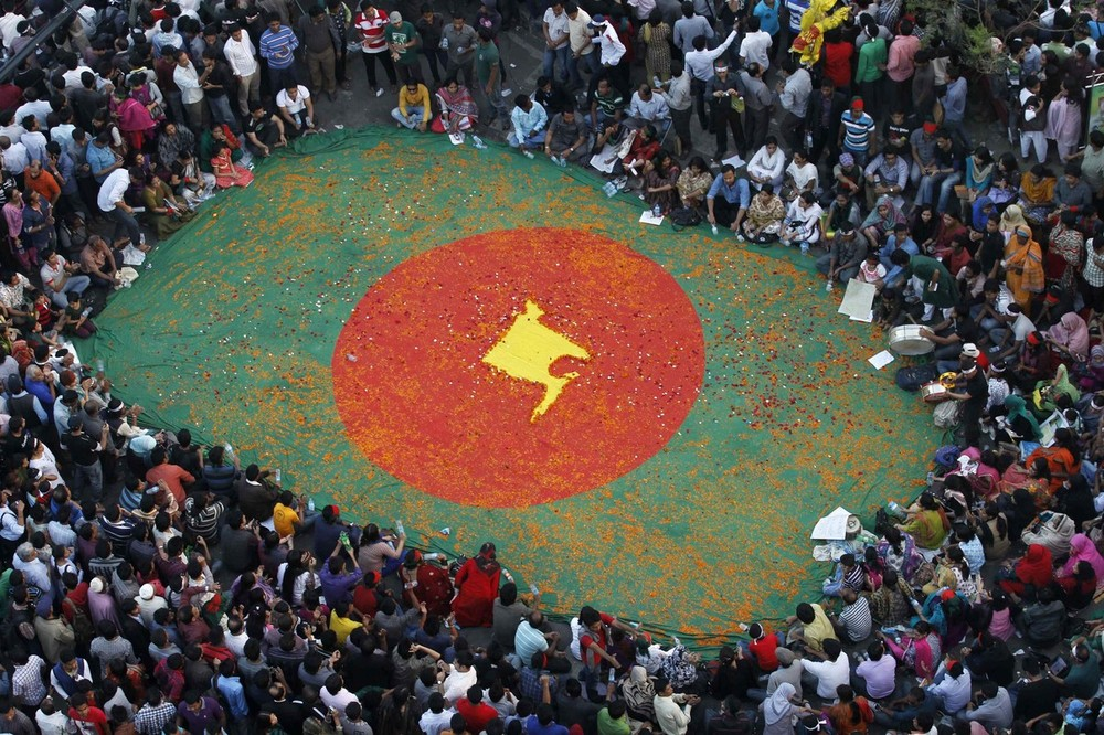 People observe a sit-in protest around a national flag of Bangladesh with a map of the country on it, made by flowers, as they attend a mass demonstration at Shahbagh intersection in central Dhaka. Tens of thousands of demonstrators have been camping in