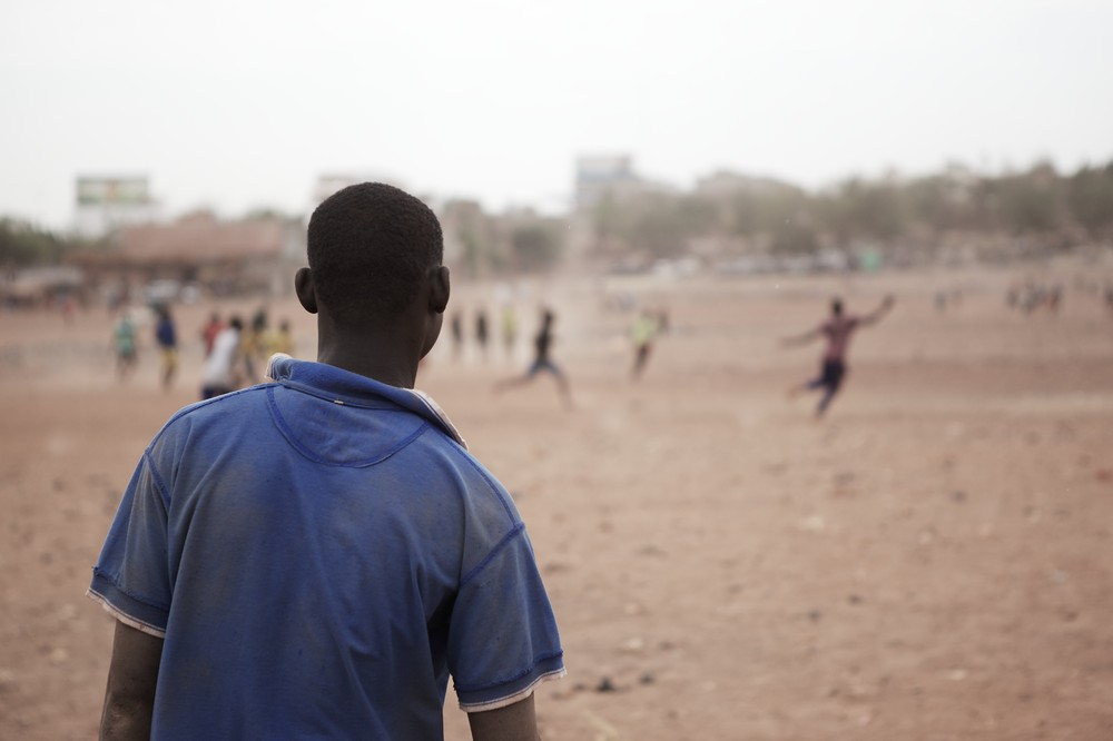 A man watches as a local football team plays a match in the area of Badalabougou, in Bamako.
