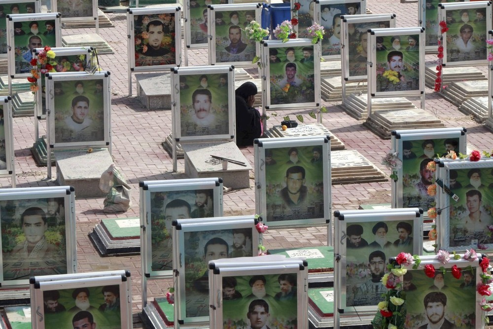 Relatives visit graves in the Mahdi Army cemetery in the holy city of Najaf, Iraq. The country marked the 10th anniversary of the US-led invasion that ousted former leader Saddam Hussein on Tuesday.