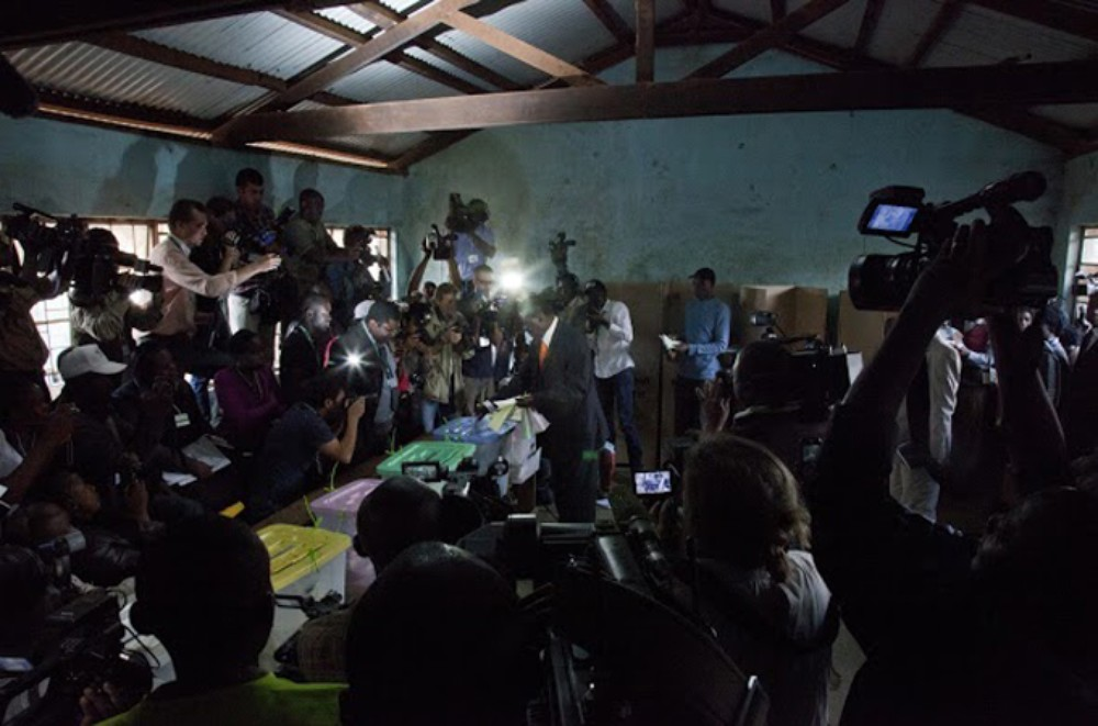 Press surround candidate Raila Odinga as he voted at the Kibera primary school