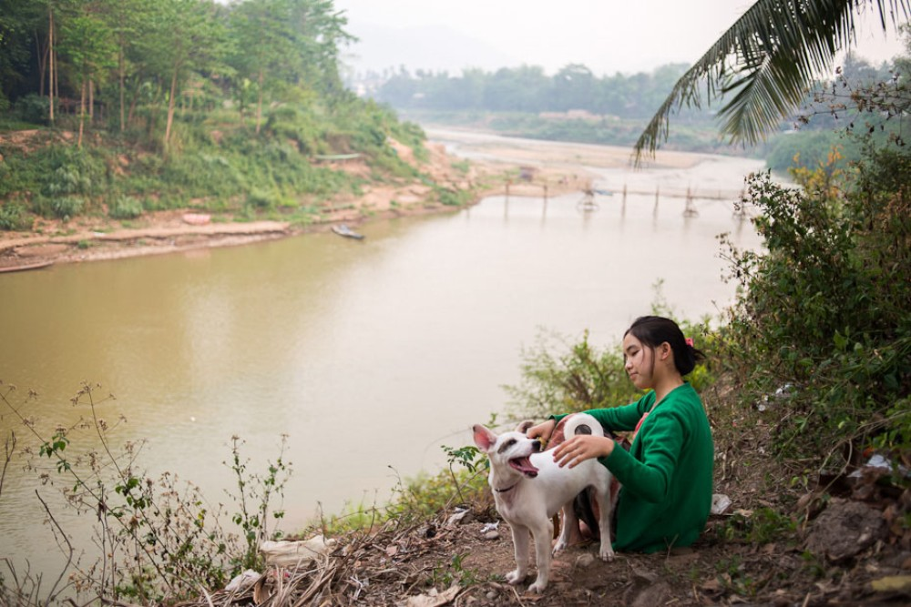 A young girl and her puppy sit high on the banks the Nam Kham River, a tributary of the Mekong. Laos is going ahead with building a number of dams on the Mekong and its tributaries, despite objections from the governments of Cambodia and Vietnam and concerns from environmental groups.