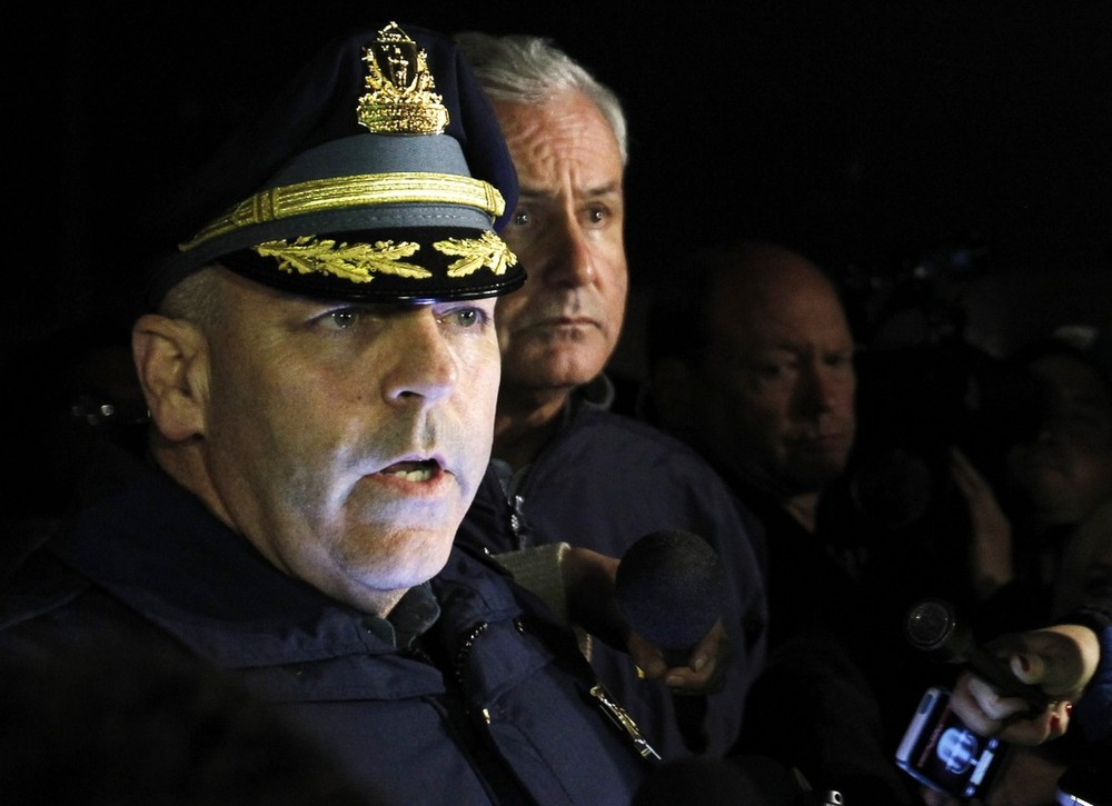 Massachusetts State Police Timothy Alben, left, speaks to reporters on Friday about the status of the two suspects in the Boston Marathon bombings in Watertown, Massachusetts [Reuters]