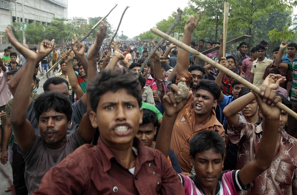Bangladeshi garment workers shout slogans and block a road during a protest against the collapse of an eight-storey building in Dhaka that housed several garment factories, killing more than 300 people. The owner of the building, who ignored inspectors who advised to close the structure when cracks appeared in the building a day before the collapse,  sits at the nexus of party politics and the country\(***)s powerful $20bn billion garment industry.