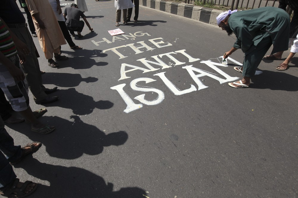 "A man paints the slogan ""Hang the Anti-Islam"" on the street before attending a rally in Dhaka, Bangladesh. The march, called by hardline group Hefajat-e-Islam, was to demand action against ""atheists and blasphemous bloggers"" who they say are defaming Islam."
