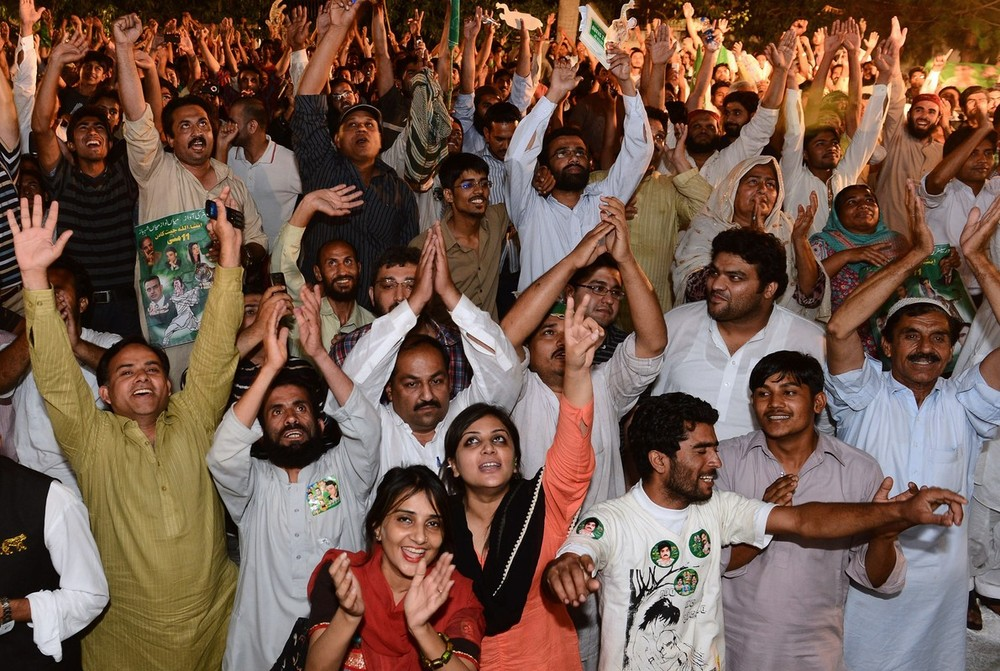 Supporters of former Pakistani Prime Minister and head of the Pakistan Muslim League-N (PML-N) Nawaz Sharif, cheer as they listen to him outside his residence after his party victory in general election in Lahore on May 11, 2013. Sharif declared victory for his centre-right party in Pakistan\(***)s landmark elections, as unofficial partial results put him on course to win a historic third term as premier.