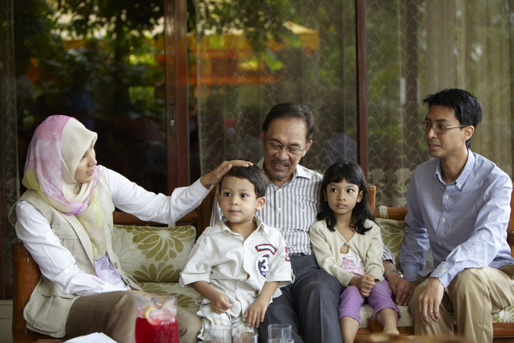 Opposition leader Anwar Ibrahim relaxes with his family before the final stretch of the election campaign. He is pictured here with his daughter, Nurul Izzah, her husband and their two children.