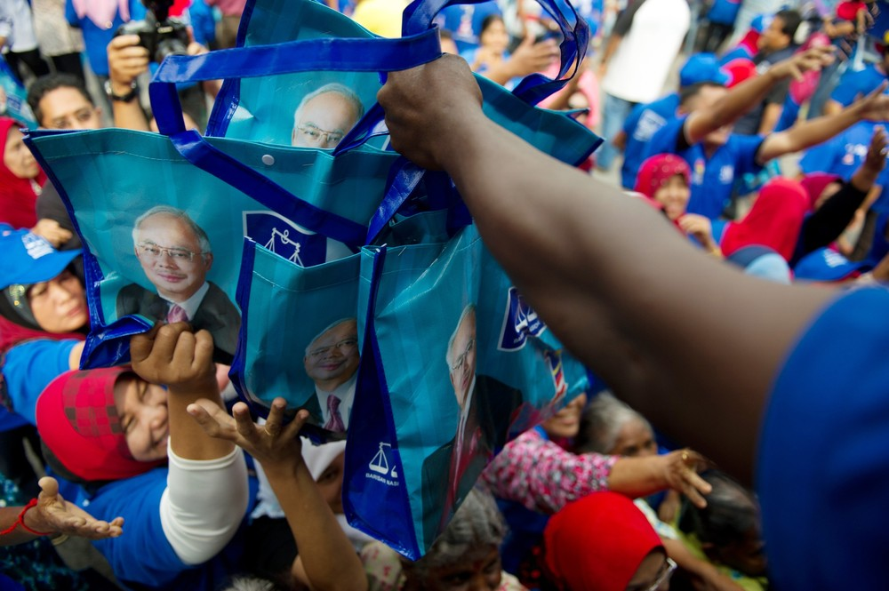 <p>Supporters receive goody bags before the arrival of Malaysia(***)s Prime Minister Najib Razak, president of the ruling Barisan Nasional coalition, during a campaign event ahead of the country(***)s general elections. Voters went to the polls today to decide an election that has polarised the nation of 28 million people.</p>