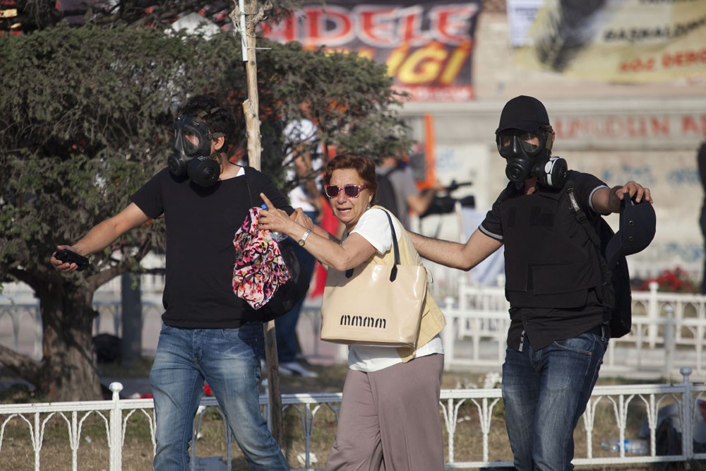 <p>Plain clothes policemen help a tourist to get away from tear gas as Turkish police raid Taksim Square this morning. Since the protests began, a once healthy tourism industry is now at a standstill.</p>
