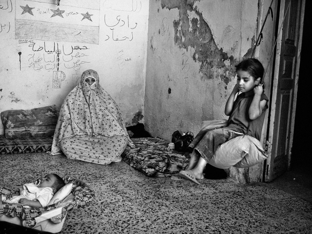 Nine-year-old Rania, right, sits on a swing inside her extended family\(***)s home in East Amman, an area where many Syrian refugees have rented apartments. Her father and all the men in the family are still in Syria.