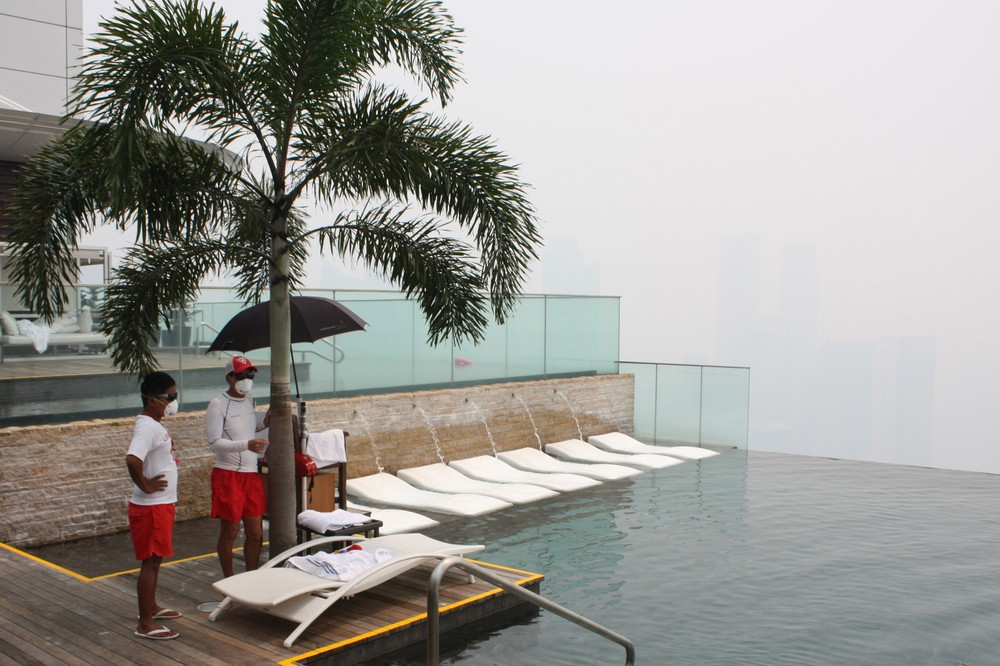 <p>Two lifeguards wear masks at a swimming pool on the top floor of the Marina Bay Sands Hotel as haze hits Singapore. </p>