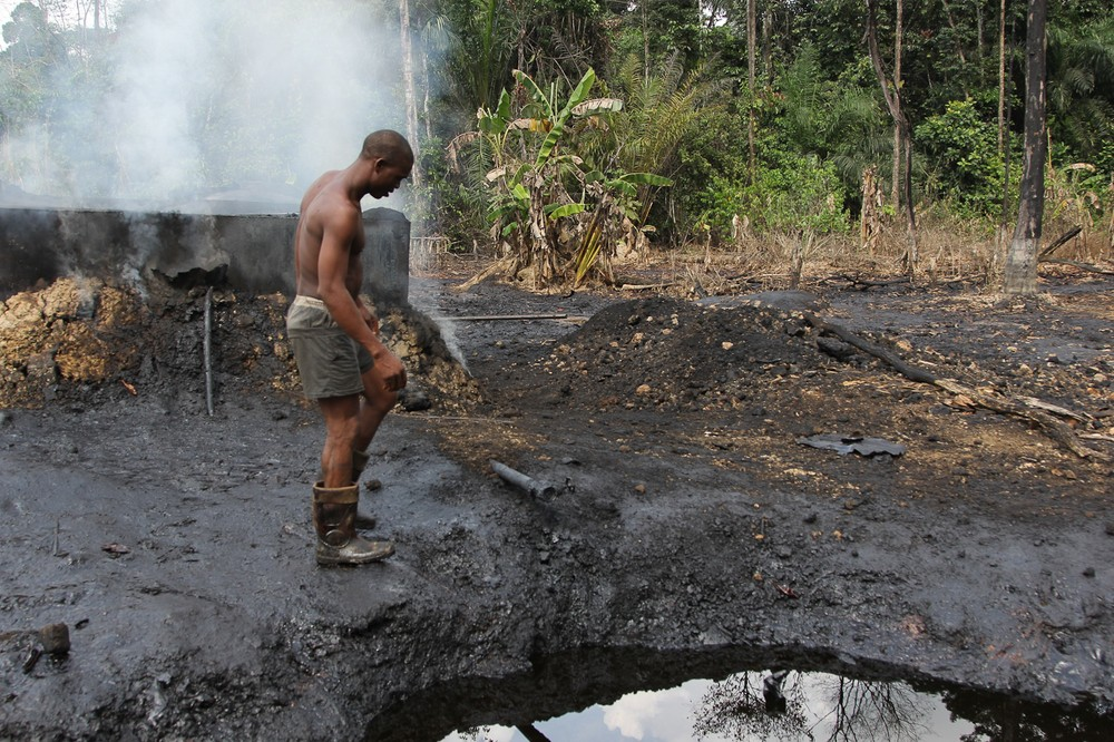 A worker at an illegal refinery camp inspects refinery equipment  