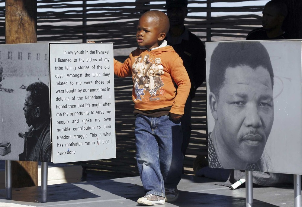 A boy stands next to a picture of former South Africa\(***)s president Nelson Mandela at a museum in Mvezo during former president Mandela\(***)s 92nd birthday celebrations, about 70km from Mthatha, in the Eastern Cape July 18, 2010.