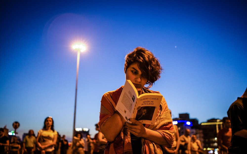 <p>A woman reads the philosophical essay <em>The Myth of Sisyphus</em> by French author Albert Camus in Taksim Square. The book focuses on the search for meaning in the absence of God.</p>