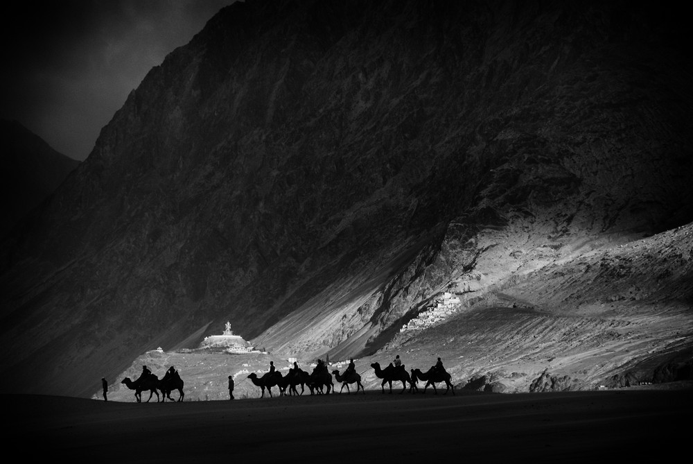 <p>Camels walk across white sand dunes with the Diskit Monastery, the oldest and largest Buddhist monastery in Nubra Valley, in the distance. Nearby is the Siachen Glacier, over which both India and Pakistan claim sovereignty.</p>