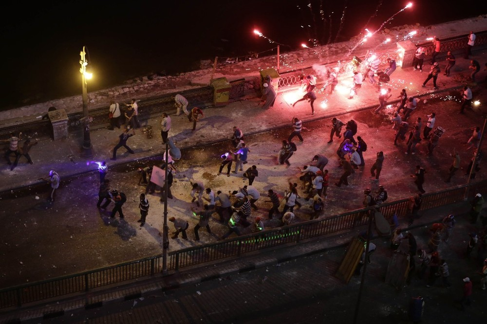 <p>Supporters and opponents of Egypt\(***)s ousted president, Mohammed Morsi, clash near Maspero, where Egypt\(***)s state TV and radio station is located, in Cairo on July 5.</p>