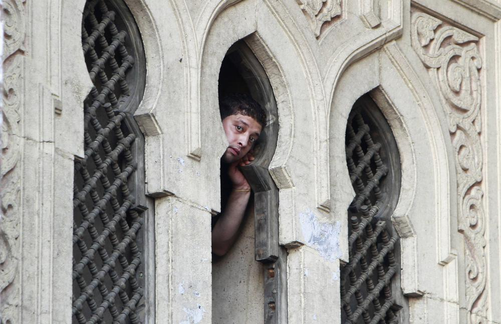 A protester looks through a window of the Fateh mosque.