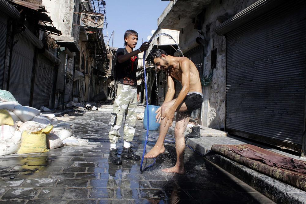 A Free Syrian Army fighter takes a shower in the old city of Aleppo on September 1, 2013. The week has seen a dramatic ramping-up of international rhetoric after suspected chemical weapons use prompted several Western nations to consider military intervention in Syria [REUTERS]