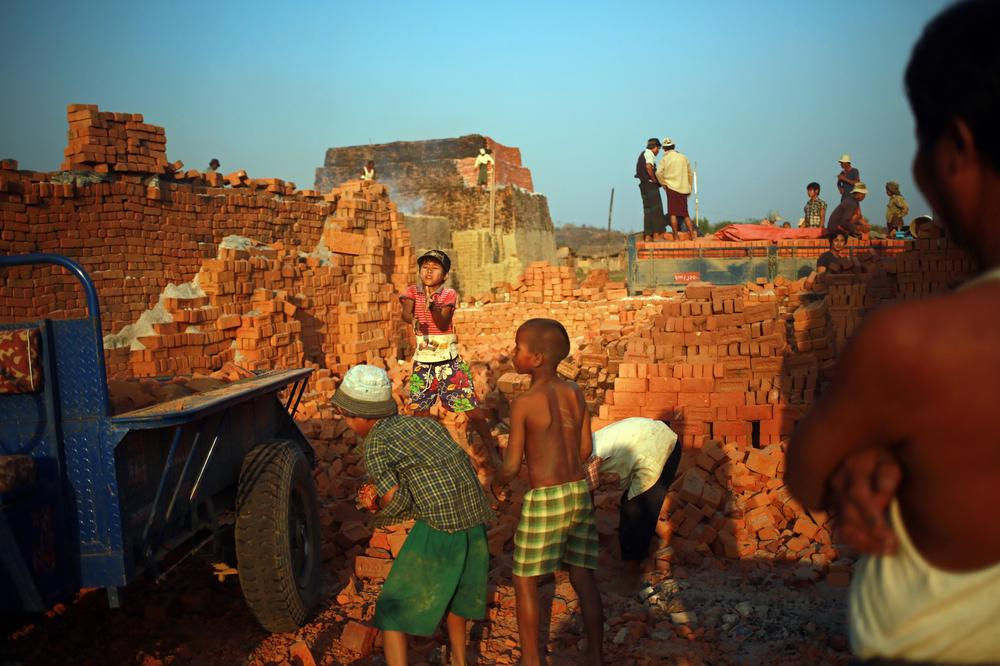 Child workers carry bricks to transport to construction sites at a brick factory.