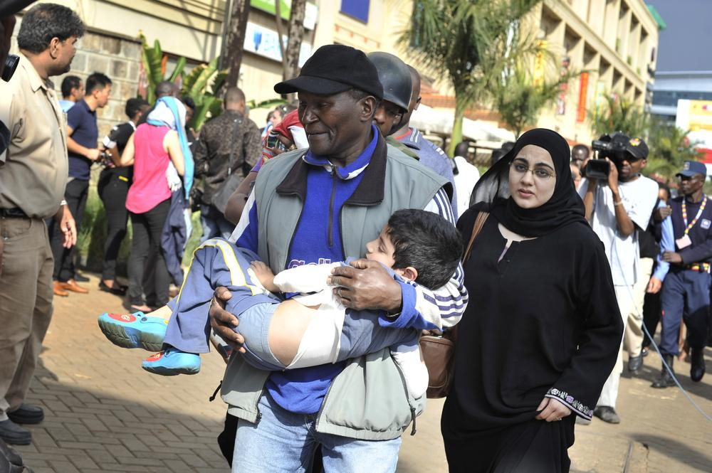 A rescue worker helps a child outside the Westgate Mall in Nairobi, Kenya Saturday, September 21, 2013, after Al Shabaab gunmen opened fire and reportedly threw grenades during an attack that left dozens dead and wounded.