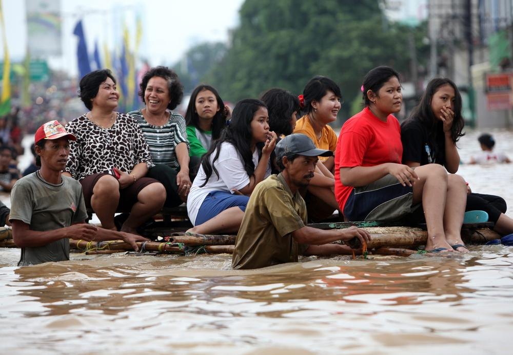Indonesians make their way through a flooded area in Jakarta on January 19. Dozens of villages of 18 districts in Jakarta are flooded due to rain since January 11, causing more than 5,000 people to evacuate. The floods killed at least four people this week in Jakarta.