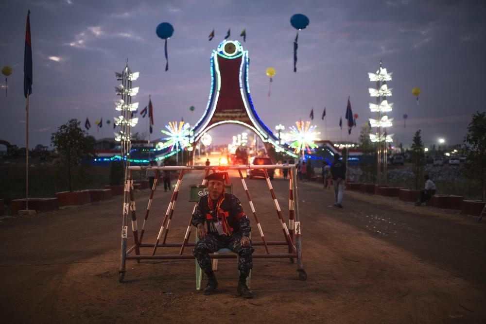 <p>A Border Guard Force (GBF) soldier sits in front of the camp ground entrance where the Karen New Year festival celebration took place in Kokko Myaing village.</p>