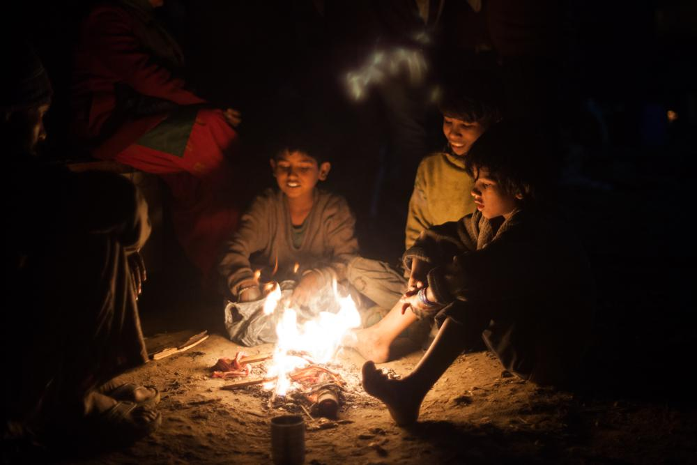Bare foot children group around a fire to keep warm. About 900 people, including about 500 children, have been left without shelter after their shanties were demolished by authorities in north east Delhi.