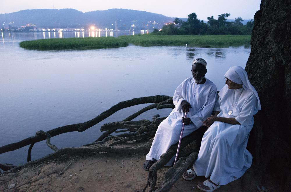 Imam Moussa Bawa, 72, and Sister Maria Concetta, 80, converse on the banks of the Oubangi River in Zongo, DRC. The two religious leaders attempt to heal the wounds that have divided the Christian and Muslim communities in Central Africa Republic.