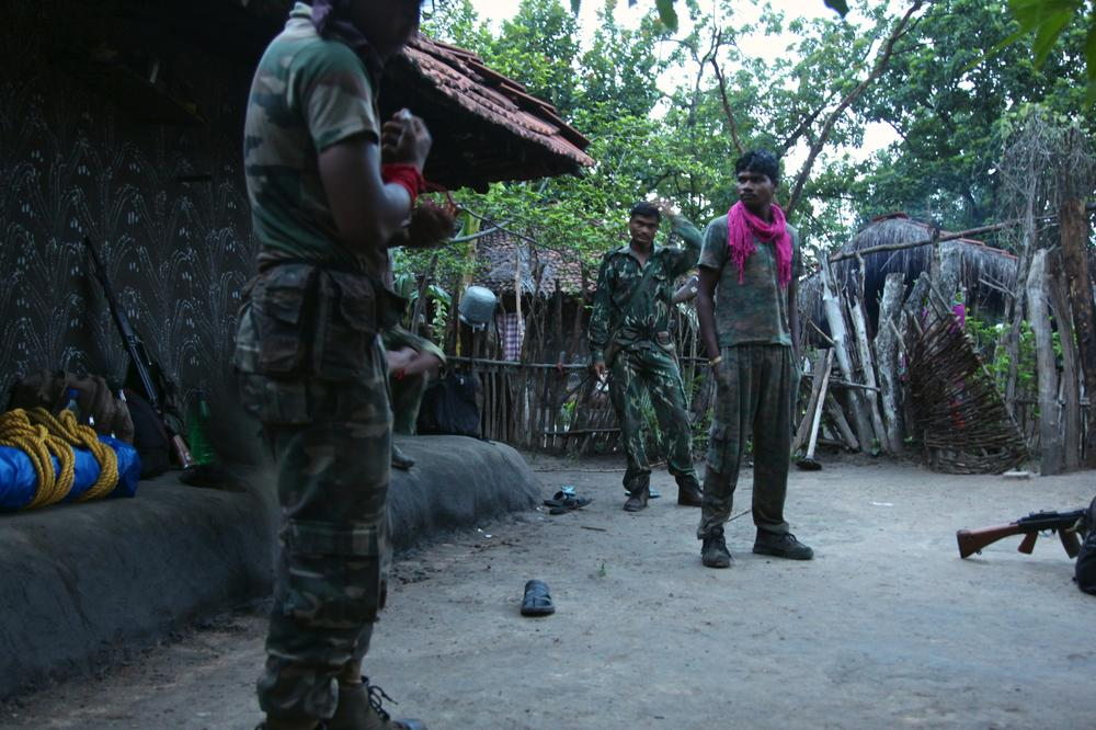 Camped overnight at Konjed village, policemen prepare to resume their patrol. They use red armbands as identification to prevent friendly fire.