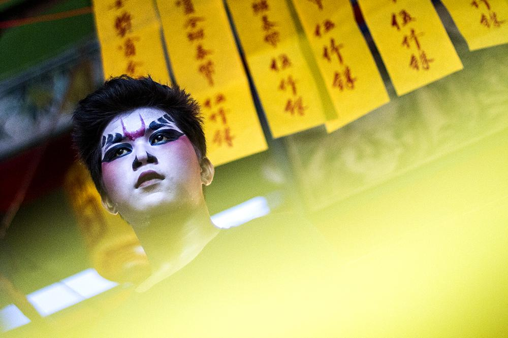A Chinese opera performer waits on the stage before the show.