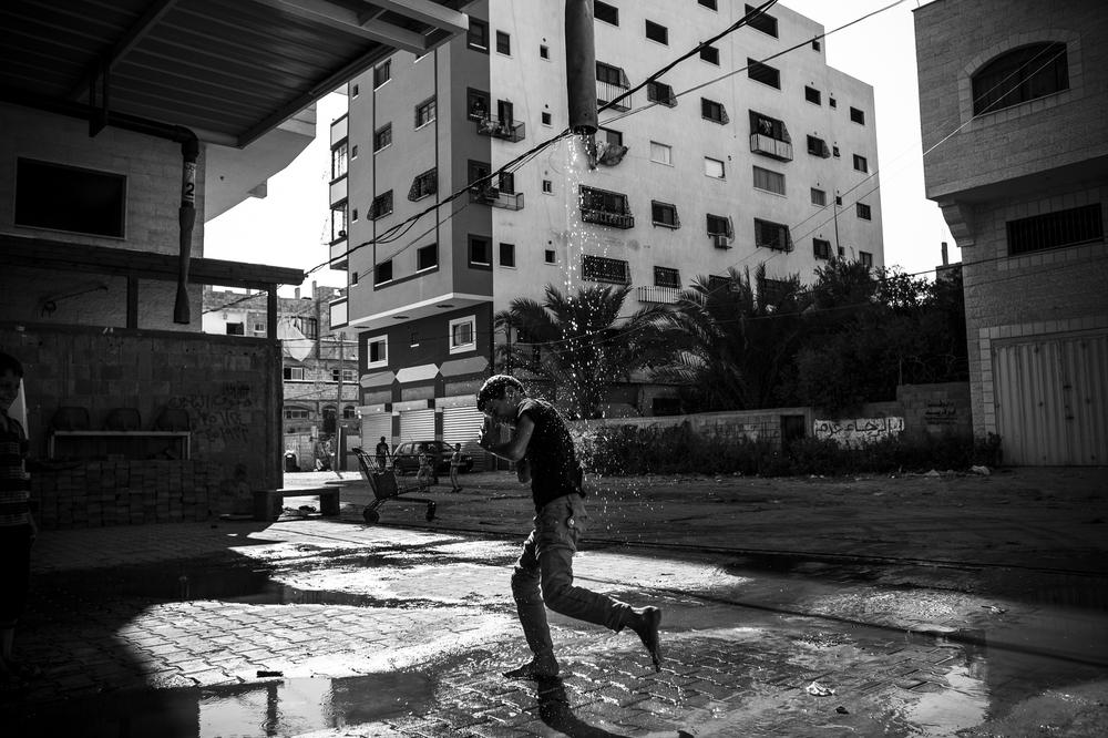 A boy plays at a water pump in central Gaza City.