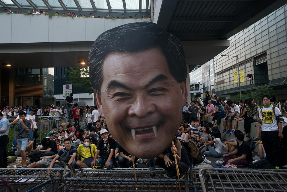 A protester holds a defaced picture of Hong Kong Chief Executive Leung Chun-ying during the occupation of government headquarters in Admiralty district on Saturday.
