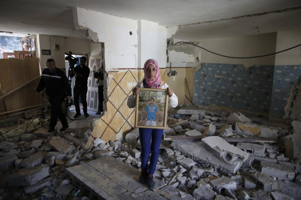 A relative of Abdel Rahman al-Shaludi, a Palestinian who killed two Israelis with his car last month, displays his portrait inside his family home after it was razed by Israeli authorities in East Jerusalem(***)s Silwan neighbourhood as Israel stepped up its controversial demolition policy.
