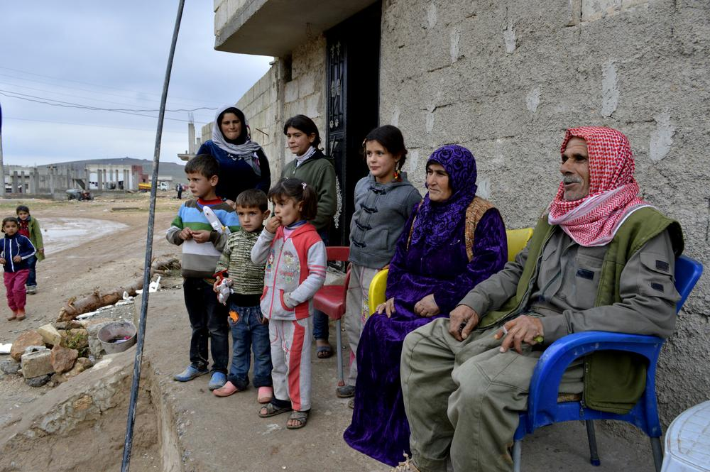 <p>Aladdin Abdo, 64, and his wife Amish Ahmed, 55, sit in front of their son(***)s house in Kobane surrounded by their children and grandchildren. Abdo is now a member of the Kurdish force in the besieged town.</p>