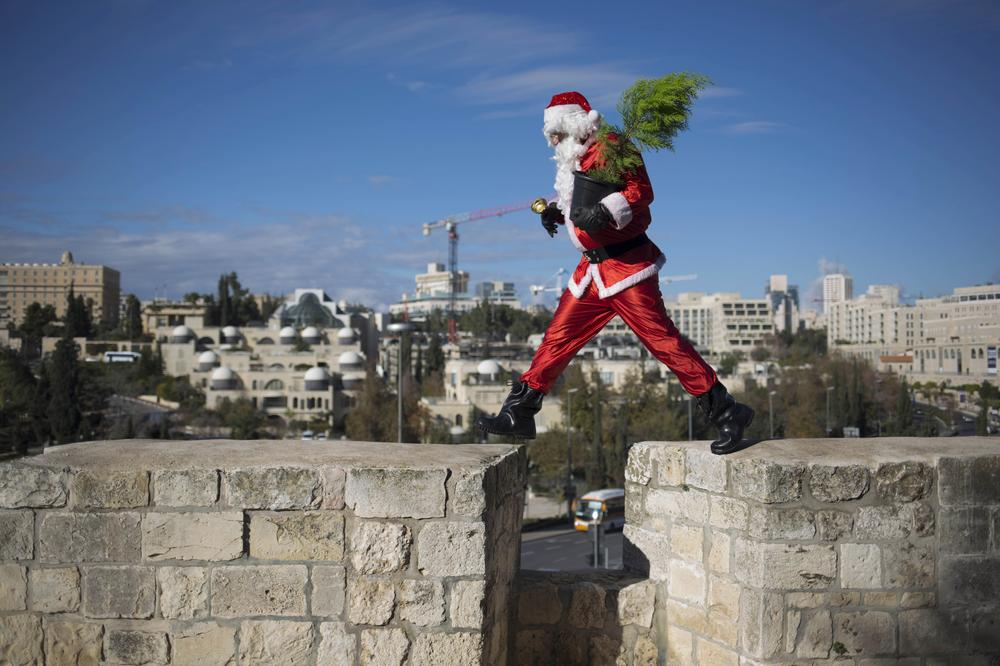 A man dressed as Santa Claus walks on the wall of the Old City in Jerusalem.
