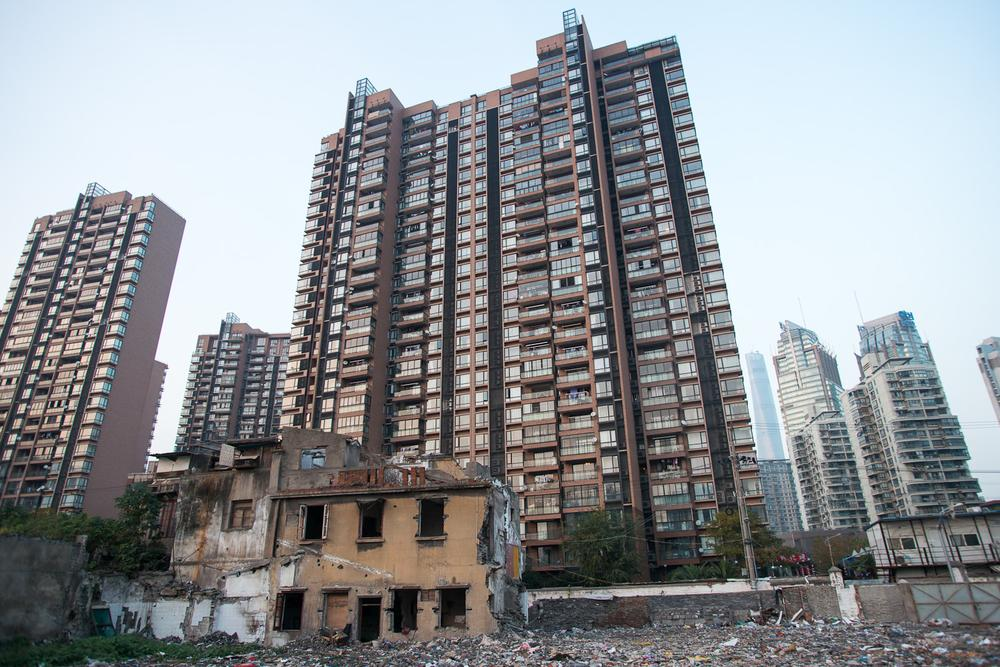 <p>A section of a colonial-era building stands on the edge of an old residential block that has been cleared to make way for more high-rise development, such as those seen in the background. </p>
