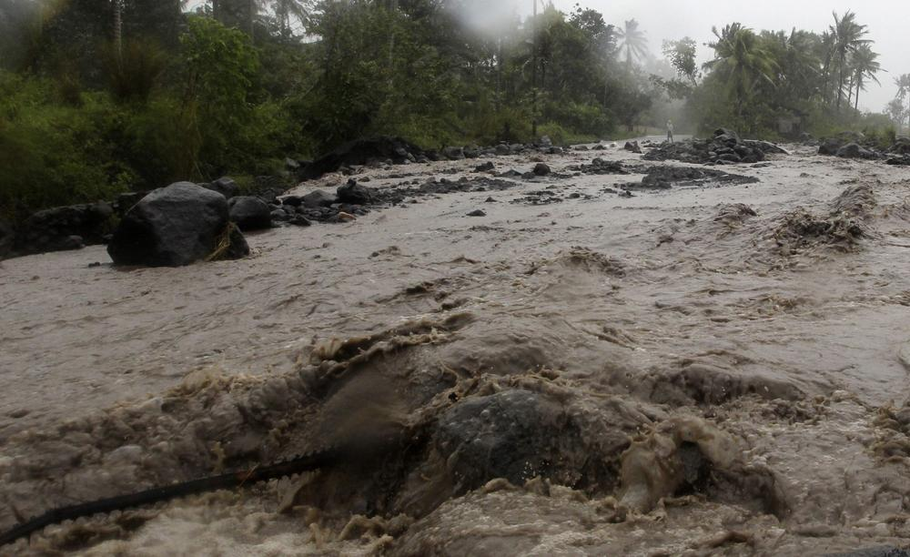 Volcanic rocks are washed onto a main road during a flash flood brought on by Typhoon Hagupit in Guinobatan, Albay province southern Luzon.