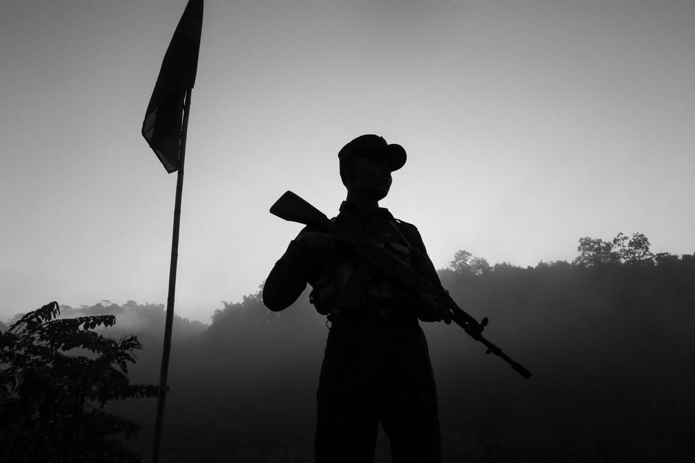 <p>A soldier stands guard on one side of the mountain while the Myanmar military is deployed on the other side.</p>