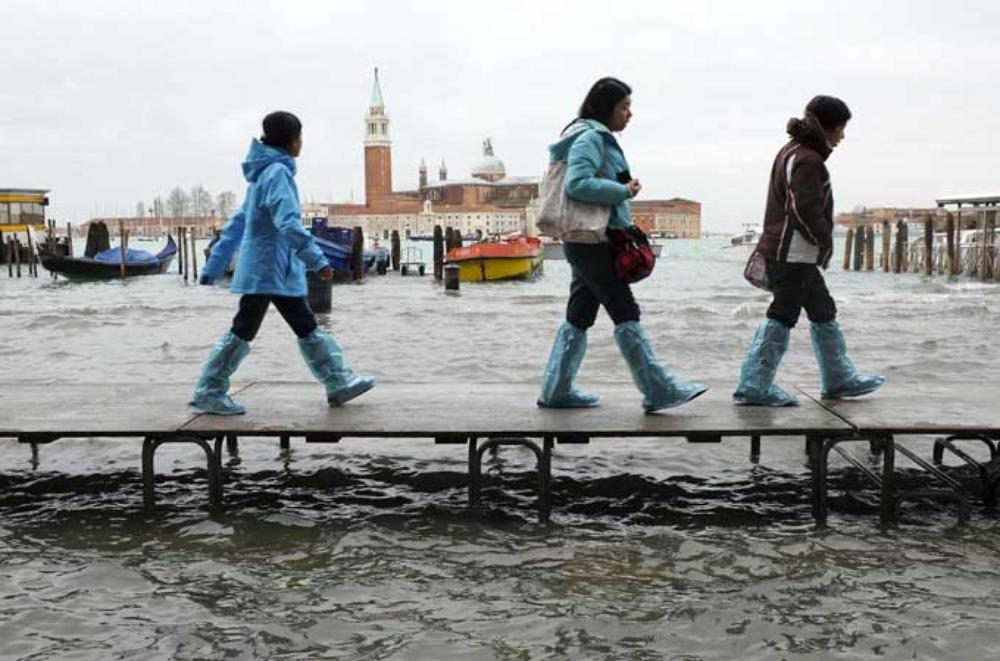 Tourists walk on raised platforms above flood waters during a period of seasonal high water in Venice, on January 31.