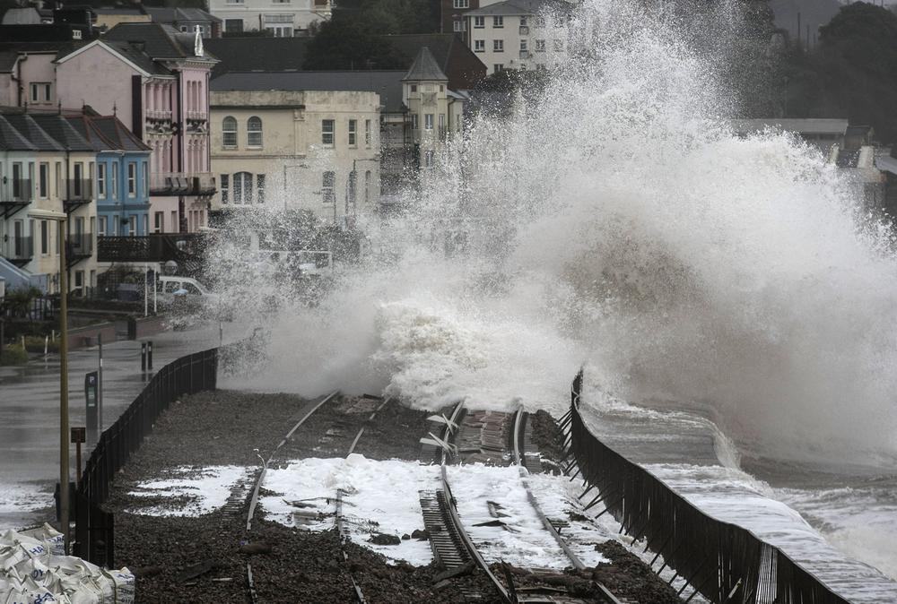 <p>Waves crash against the seafront and the railway line that has been closed due to storm damage at Dawlish on February 5 in Devon, England.</p>